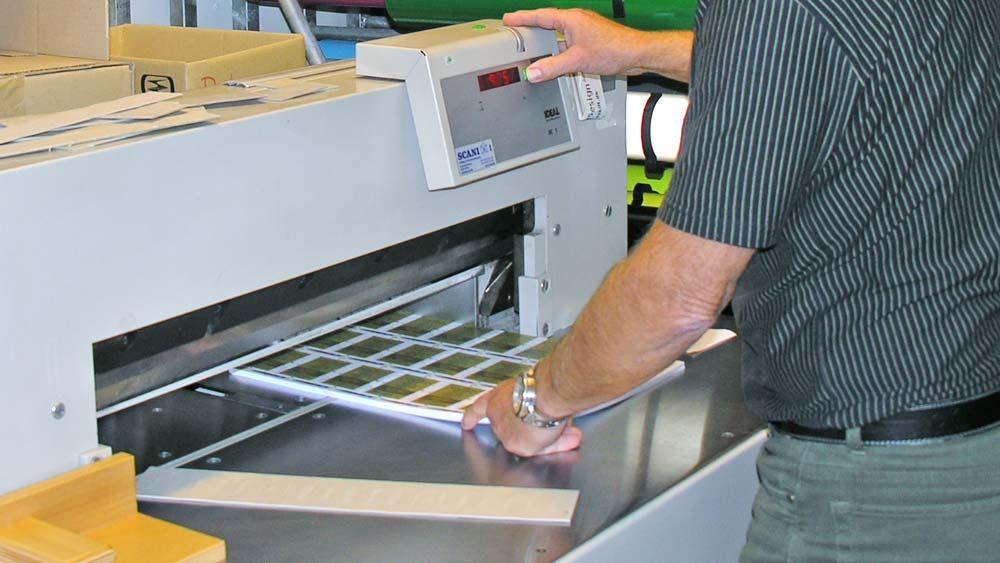 billede af person der betjener en beskæringsmaskine i forbindelse med print